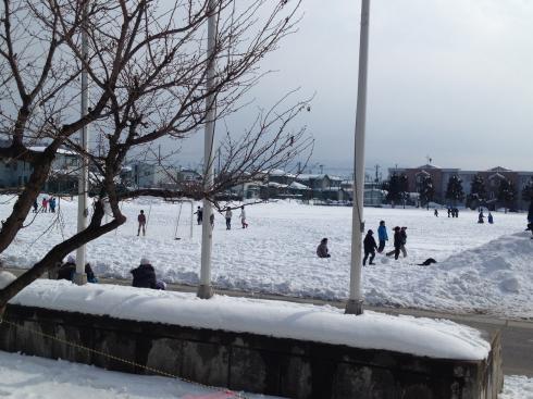 雪のグラウンドで遊ぶ子ども達
